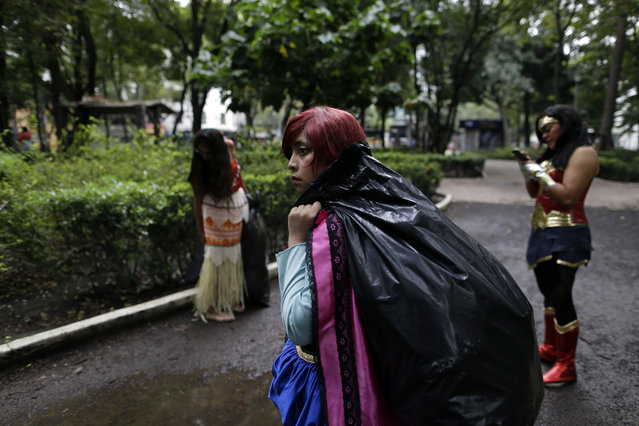 Women dressed in costumes carry presents to give out to children near buildings that collapsed during a 7.1 earthquake in Mexico City, Thursday, September 21, 2017. Tuesday's magnitude 7.1 earthquake has stunned central Mexico, killing more than 200 people as buildings collapsed in plumes of dust. (Photo by Natacha Pisarenko/AP Photo)