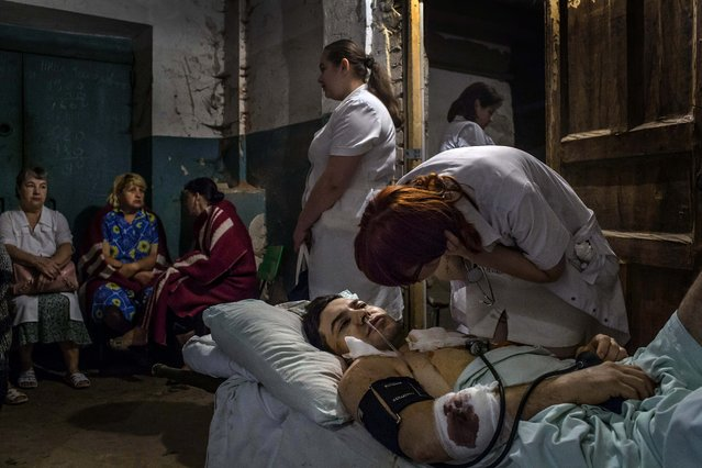 A nurse looks after Dmitry Romanenko, a hospital patient evacuated to the basement after early-morning shelling hit nearby in Donetsk, Ukraine, on August 24, 2014. (Photo by Mauricio Lima/The New York Times)