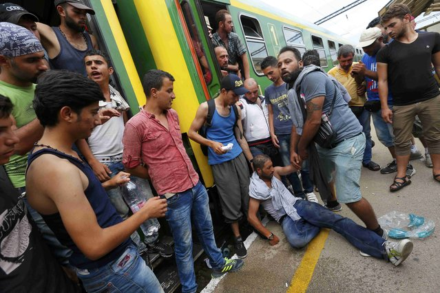 Migrants stand around a man feeling unwell at the railway station in the town of Bicske, Hungary, September 3, 2015. (Photo by Laszlo Balogh/Reuters)
