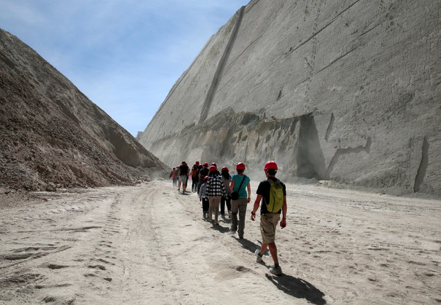 Visitors arrive at the Cal Orcko cliff which is covered with thousands of dinosaur's footprints in Cal Orcko, on the outskirts of Sucre, Bolivia, July 22, 2016. (Photo by David Mercado/Reuters)
