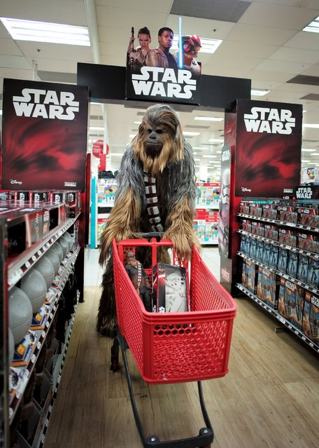 """A fan dressed as Chewbacca shops for merchandise from the upcoming film """"Star Wars: The Force Awakens"""" just before midnight on """"Force Friday"""" in Sydney, September 4, 2015. New """"Star Wars"""" toys and other merchandise were released in stores across Australia and online around the world just after midnight local time. (Photo by Jason Reed/Reuters)"""