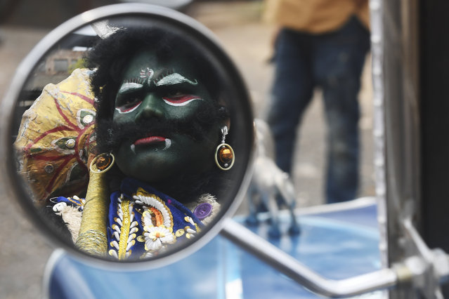 The reflection of a man dressed as Hindu deity of death Yamaraj (R) to raise awareness about the coronavirus is seen on the wing mirror of a vintage car during a government-imposed nationwide lockdown as a preventive measure against the COVID-19 coronavirus, in Kolkata on April 24, 2020. (Photo by Dibyangshu Sarkar/AFP Photo)