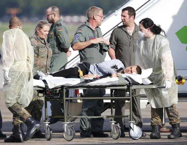 German army medical personnel attend to a wounded Ukrainian soldier in Berlin's Tegel airport, September 2, 2014. Some 19 Ukrainian soldiers wounded during fights in eastern Ukraine were brought to Berlin from Kiev on Tuesday for further medical treatment in German military hospitals. (Photo by Fabrizio Bensch/Reuters)