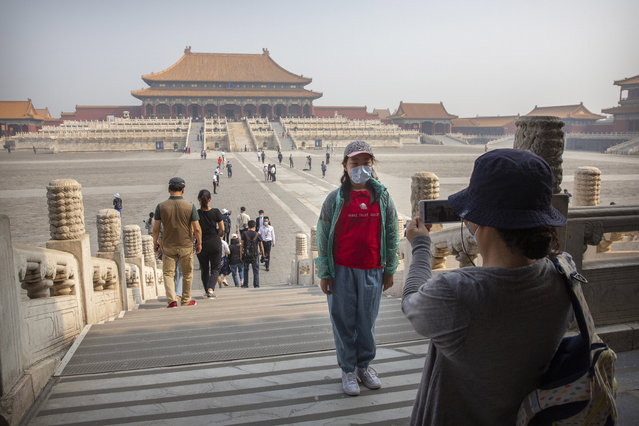 A visitor wearing a face mask to protect against the new coronavirus poses for a photo in the Forbidden City in Beijing, Friday, May 1, 2020. The Forbidden City reopened beginning on Friday, China's May Day holiday, to limited visitors after being closed to the public for more than three months during the coronavirus outbreak. (Photo by Mark Schiefelbein/AP Photo)
