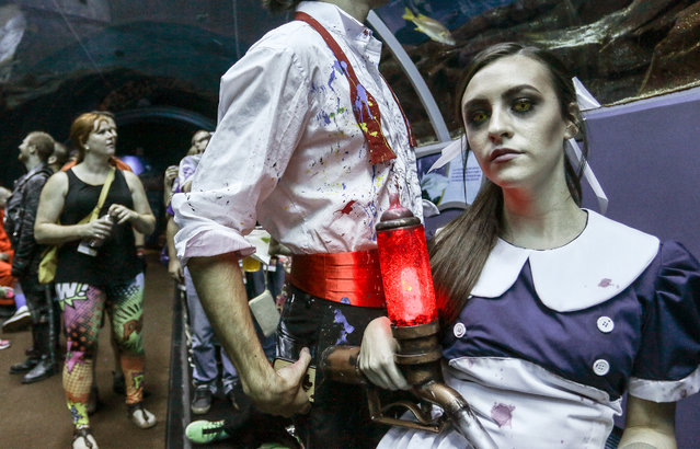 """In this Saturday, September 5, 2015, photo, a woman dressed as Little Sister, a character from the popular """"BioShock"""" video game, attends a private party held at the Georgia Aquarium as part of Dragon Con in Atlanta. The convention draws fans from around the country to take part in sci-fi and fantasy costume contests, a massive parade through downtown Atlanta and educational seminars about science and costume making. (Photo by Ron Harris/AP Photo)"""
