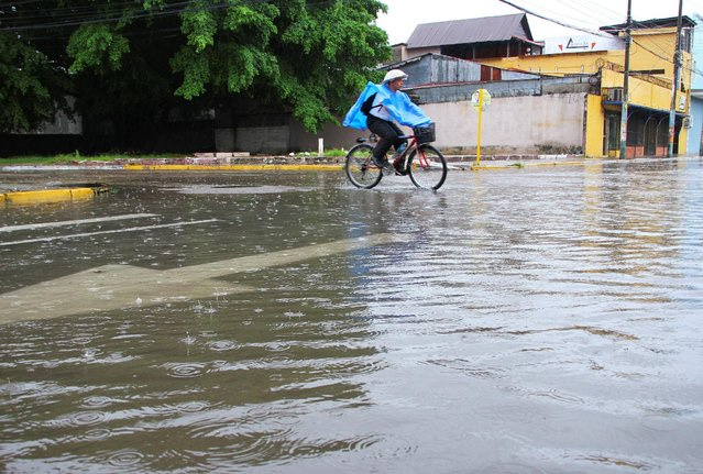 A man cycles in a flooded street as Hurricane Earl passes the coast of La Ceiba, Honduras, August 3, 2016. (Photo by Reuters/Stringer)