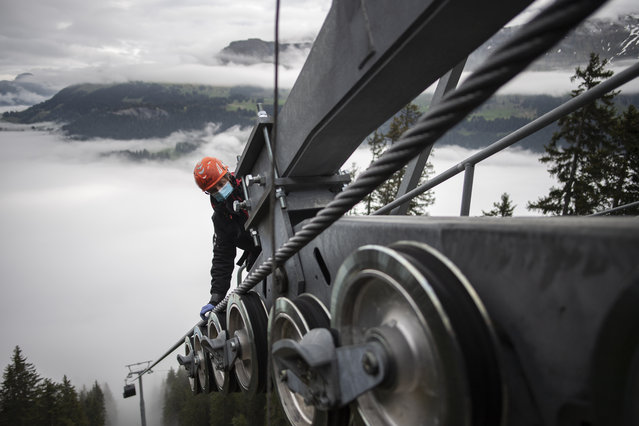 A technician wearing a protective mask during an inspection work at the Heidbuel panorama cable car, on Thursday, 14 May 2020, in Churwalden, Switzerland. Swiss mountain railways face an uncertain future due to the coronavirus crisis. (Photo by Gian Ehrenzeller/Keystone via AP Photo)