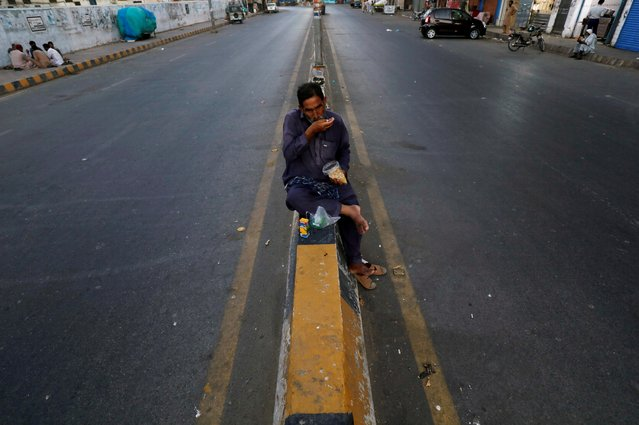 A daily wage labourer sits on the road's median barrier as he breaks fast during the Muslim fasting month of Ramadan, amid lockdown in efforts to stem the spread of the coronavirus disease (COVID-19), in Karachi, Pakistan on April 29, 2020. (Photo by Akhtar Soomro/Reuters)