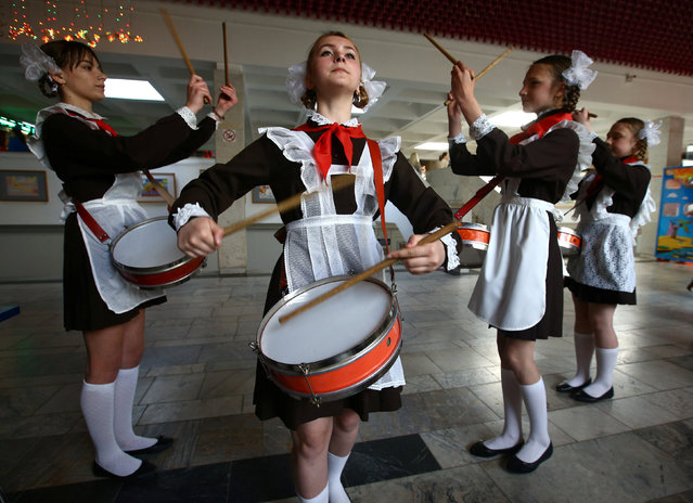 Belarusian schoolchildren, who are members of a pro-government Young Pioneer movement, perform with drums as they take part in a meeting to mark the 95th anniversary of their organisation in Minsk, Belarus May 19, 2017. (Photo by Vasily Fedosenko/Reuters)