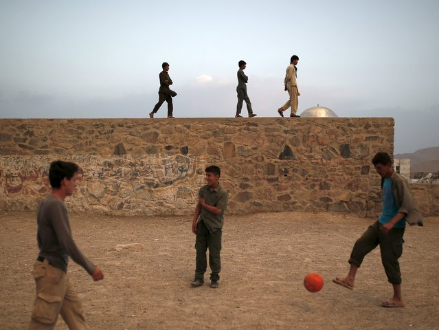 Men walk on a wall while others play football during sunset in Kabul, Afghanistan August 24, 2015. (Photo by Ahmad Masood/Reuters)