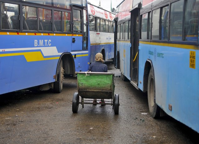 A porter sits in his pushcart as he waits for customers in between passenger buses at a municipal bus terminal in Bengaluru, India, September 8, 2015. (Photo by Abhishek N. Chinnappa/Reuters)