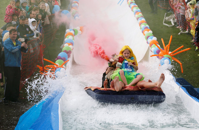"Participants hold smoke flares as they slide down along a chute to cross a pool of water and foam during the ""Letniy Gornoluzhnik"" (Summer mountain puddle rider) festival at the Bobroviy Log Fun Park near the Siberian city of Krasnoyarsk, Russia, August 21, 2016. (Photo by Ilya Naymushin/Reuters)"