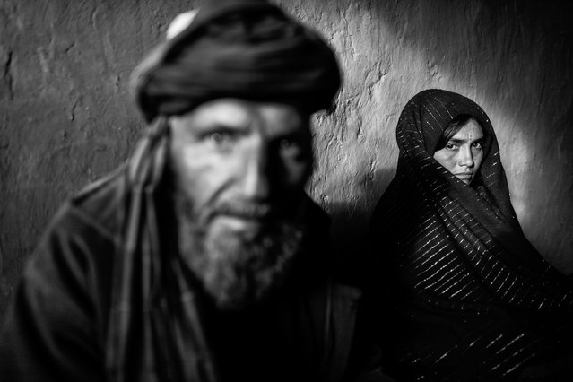 A young Afghan woman standing beside her much older husband. (Photo by Majid Saeedi/Getty Images)