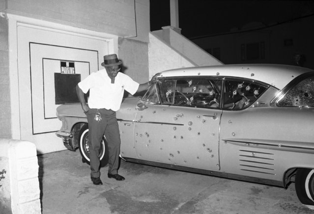 Howard Bacon, 54, of 1600 Newcomb St., San Francisco, was standing on the porch of his home when a black sniper jumped behind his car and started firing at police in San Francisco, September 28, 1966. They responded in kind and Bacon sadly looks at his damaged auto. The shooting took place near Third and Newcomb Streets in San Francisco's Bay View and Hunters Point riot area. (Photo by Robert H. Houston/AP Photo)