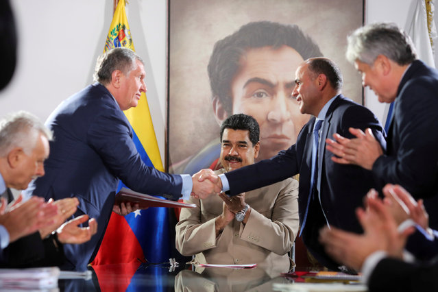 Head of Russian state oil firm Rosneft Igor Sechin (standing L) shakes hands with Venezuela's Oil Minister and President of the Venezuelan state oil company PDVSA Manuel Quevedo, in front of  Venezuela's President Nicolas Maduro, in Maiquetia, Venezuela December 16, 2017. (Photo by Reuters/Miraflores Palace)