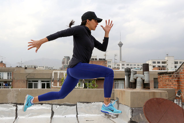 Iranian athlete Maryam Toosi practises on the rooftop of her apartment building following  the closure of sports facilities as part of measures aimed at containing the COVID-19 coronavirus, in Iran's capital Tehran on May 19, 2020. The coronavirus pandemic has forced the world's athletes to keep fit in confinement. The novel coronavirus has claimed the lives of nearly 7,200 people in Iran, making it the deadliest outbreak in the Middle East. The government ordered the closure of sports facilities in mid-March as part of measures aimed at containing the virus. (Photo by Atta Kenare/AFP Photo)
