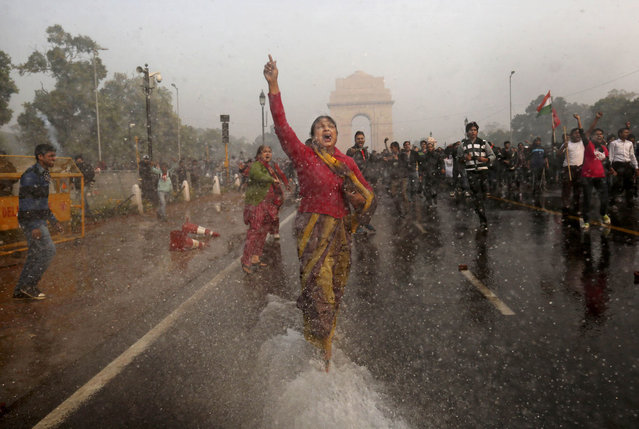 A female protester shouts as she is hit with an Indian police water cannon during a violent demonstration near the India Gate against a gang rape and brutal beating of a 23-year-old student on a bus last week, in New Delhi, on December 23, 2012. The attack last Sunday sparked days of protests across the country. (Photo by Kevin Frayer/AP Photo)