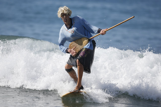 David Nickerson, 24, rides a wave dressed as Mrs Doubtfire during the 7th annual ZJ Boarding House Haunted Heats Halloween surf contest. (Photo by Lucy Nicholson/Reuters)