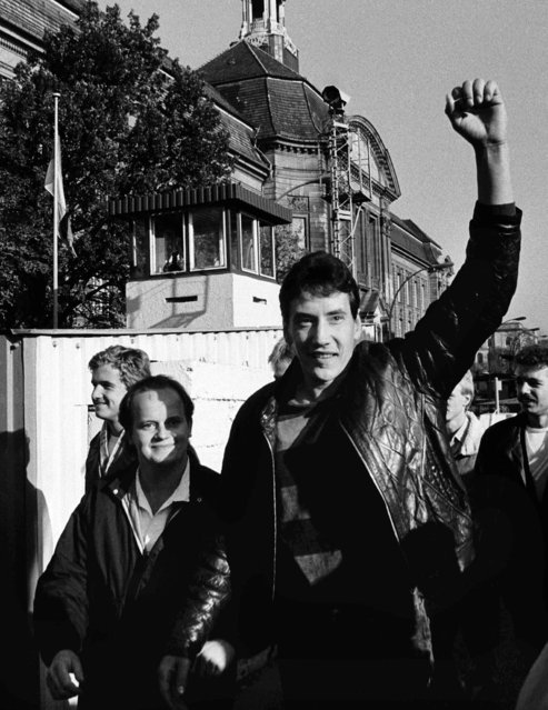 An East German man raises up his fist as he passes the border at the checkpoint Invaliden Strasse after the opening of the East German border was announced, November 10, 1989. (Photo by Reuters)