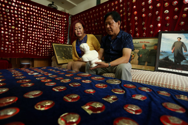 A man holds a statue of China's late Chairman Mao Zedong, as he presents his collections at his home, ahead of Mao's 40th death anniversary, in Zhangye, Gansu Province, China, September 8, 2016. (Photo by Reuters/Stringer)