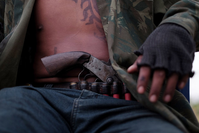 "Guardian of the Forest Paulo Paulino Guajajara, 22, wears a pistol while hanging out a a school house that serves as a base in Araribóia Indigenous Reserve, Maranhão, Brazil on August 8, 2015. He said ""My mother worries a lot about me, but it is the way you have to go"".  Loggers have been stealing hardwood trees from indigenous lands in Brazil. (Photo by Bonnie Jo Mount/The Washington Post)"
