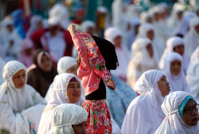 A girl adjusts her headscarf before the start of prayers for the Muslim holiday of Eid Al-Adha outdoors in Jakarta , Indonesia September 12, 2016. (Photo by Darren Whiteside/Reuters)