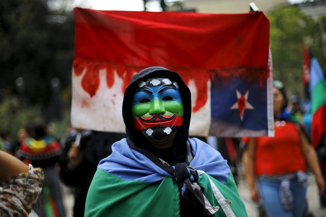 A Mapuche Indian activist wears a Guy Fawkes mask painted with the Mapuche flag during a protest march by Mapuche Indian activists against Columbus Day in downtown Santiago, Chile, October 12, 2015. (Photo by Ivan Alvarado/Reuters)
