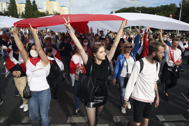 Protesters carry a giant old Belarusian national flag during a Belarusian opposition supporters' rally protesting the official presidential election results in Minsk, Belarus, Sunday, September 13, 2020. (Photo by TUT.by via AP Photo)