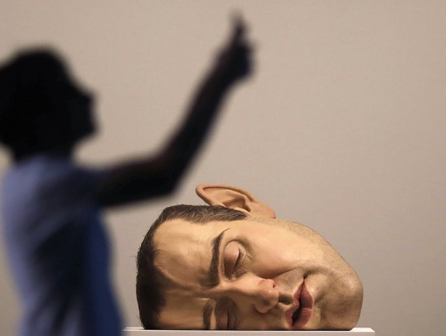 """A man takes pictures in front of a sculpture titled """"Mask II"""" by Australian sculptor Ron Mueck during a preview of his exhibition at the Pinacoteca  Museum in Sao Paulo November 19, 2014. (Photo by Nacho Doce/Reuters)"""