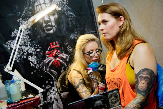 A client has a tattoo drawn on her arm at the International London Tattoo Convention in London, Britain September 23, 2016. (Photo by Linda Nylind/The Guardian)