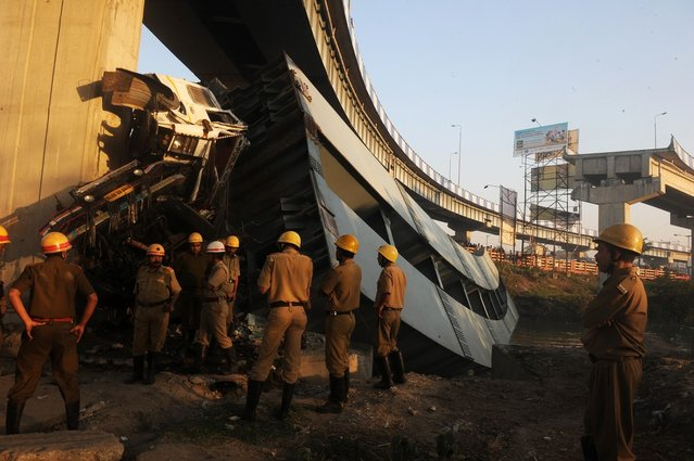 Indian onlookers and firefighters stand near the collapsed portion of the flyover in Kolkata on March 3, 2013. A huge portion of a flyover on the eastern side of the Indian metropolis collapsed leaving three persons injured, the flyover connects the airport with Eastern Metropolitan Bypass and the eastern and southern suburbs.   As the debris fell into a canal running below the flyover, it took down a truck the driver and two others were rescued from the canal by fire-brigade personnel and locals. (Photo by Dibyangshu Sarkar/AFP Photo)