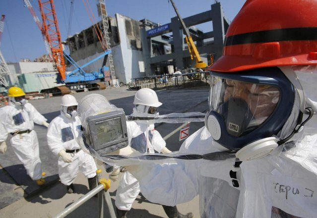 A radiation monitor indicates 114.00 microsieverts per hour near the building housing the plant's No. 4 reactor, center, and an under construction foundation, right, which will store the reactor's melted fuel rods at Tokyo Electric Power Co.'s tsunami-crippled Fukushima Dai-ichi nuclear power plant in Okuma, Fukushima prefecture, Wednesday, March 6, 2013, ahead of the second anniversary of the March 11, 2011 tsunami and earthquake. Some 110,000 people living around the nuclear plant were evacuated after the massive March 11, 2011, earthquake and tsunami knocked out the plant's power and cooling systems, causing meltdowns in three reactors and spewing radiation into the surrounding air, soil and water. (Photo by Issei Kato/AP Photo/Pool)