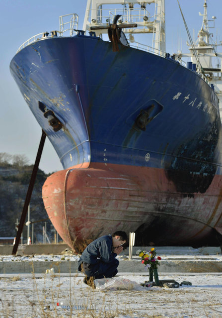 A man prays to mourn victims of the March 11, 2011, earthquake and tsunami in front of a ship brought ashore by the disaster in Kesennuma, Miyagi Prefecture, Japan.  (Photo by Kyodo via Reuters)