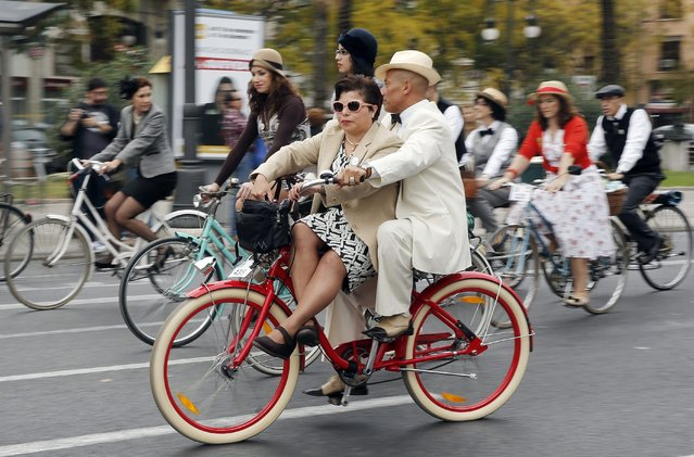 People take part in the Classic Ride Rally in downtown Valencia, eastern Spain, 23 November 2014. Some hundred people on classic bikes from the 20's to the 70's participated in the rally. (Photo by Kai Foersterling/EPA)