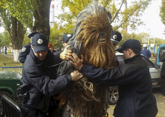 Policemen detain a person dressed as Star Wars character Chewbacca during a regional election near a polling station in Odessa, Ukraine, October 25, 2015. Ukrainians go to the polls on Sunday to appoint mayors and council heads to regional seats. The person was detained for illegal election-day campaigning, according to local media. (Photo by Ihor Babak/Reuters)