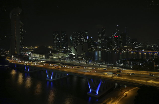The Singapore city-skyline is seen in darkness against the lit highway as lights in major buildings around the financial district are switched off for a whole hour on Saturday, March 23, 2013 in Singapore. More than 100 buildings, locations and organizations in Singapore switched off their lights as part of the global Earth Hour initiative by World Wide Fund for Nature (WWF) along with other national monuments around the world. (Photo by Wong Maye-E/AP Photo)