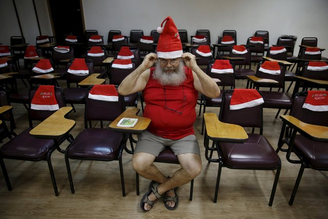 "A student of the ""Escola de Papai Noel do Brasil"" (Brazil's school of Santa Claus) wears his hat before lessons in Rio de Janeiro, Brazil, October 27, 2015. (Photo by Pilar Olivares/Reuters)"