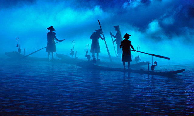 """Fishermen on the river Li in China. These boatmen participate in an illuminated display, for tourists, which takes place as evening comes. The visual effect is stunning"". (Photo by David Paul Elliott/The Guardian)"