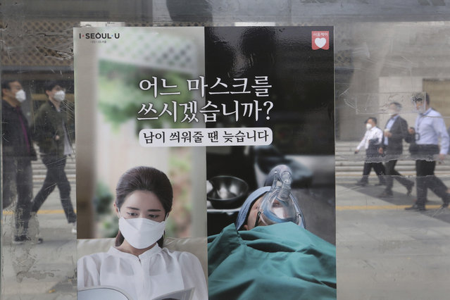 """People wearing face masks to help protect against the spread of the coronavirus walk by a poster informing mandatory mask wearing, at a bus station in Seoul, South Korea, Monday, October 12, 2020. The poster reads """"Which mask would you wear?"""". (Photo by Ahn Young-joon/AP Photo)"""