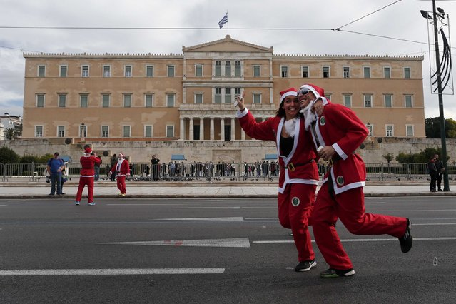 People dressed in Santa costumes run past the Greek parliament as they take part in the Santa Claus Run in Athens December 7, 2014. (Photo by Alkis Konstantinidis/Reuters)