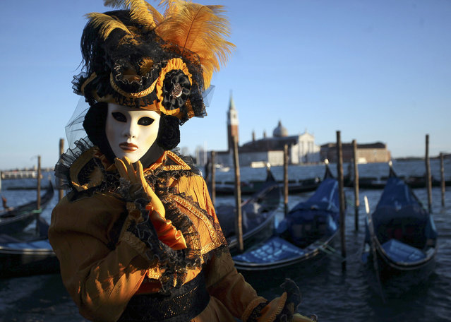 A masked reveller poses in Saint Mark's Square during the Venetian Carnival in Venice, on February 3, 2013. (Photo by Manuel Silvestri/Reuters /The Atlantic)