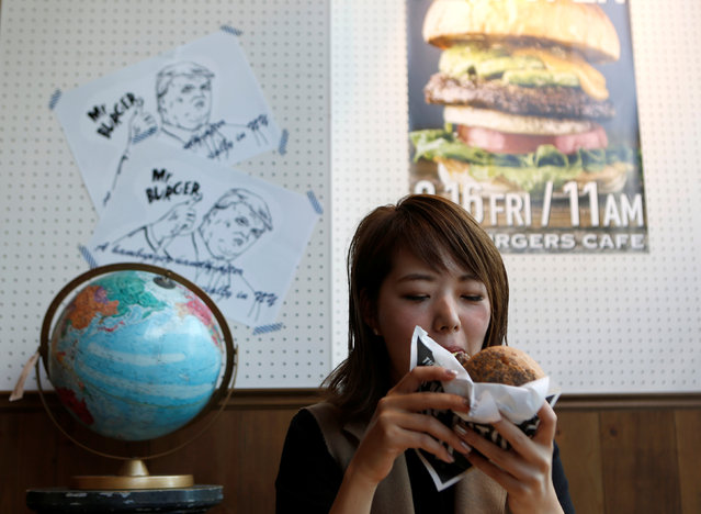 A customer Yuka Yamaura eats Mrs. Burger featuring U.S. presidential candidate Hillary Clinton at J.S. Burgers Cafe in Tokyo, Japan October 7, 2016. (Photo by Megumi Lim/Reuters)