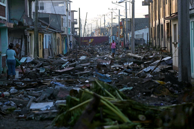 A woman walks along a street covered in debris after the passage of Hurricane Matthew in Baracoa, Cuba October 7, 2016. (Photo by Alexandre Meneghini/Reuters)
