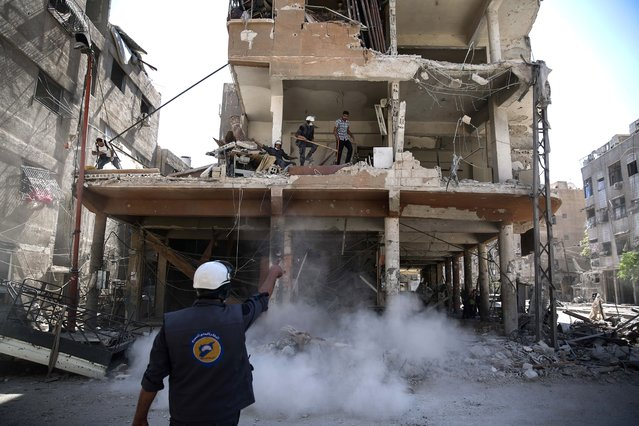 Syrian civil defence volunteers, known as the White Helmets, work around destroyed buildings following reported air strikes on the rebel-held town of Douma, on the eastern outskirts of the capital Damascus, on October 5, 2016. The White Helmets are a prominent Syrian group of emergency responders mainly made of volunteers. (Photo by Sameer Al-Doum/AFP Photo)