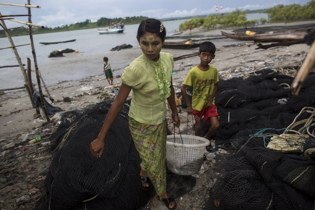 A girl and boy carry a basket of fish in Kyaukpyu township, Rakhine state, Myanmar October 6, 2015. (Photo by Soe Zeya Tun/Reuters)
