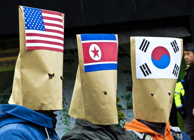South Korean protesters wearing masks made out of envelopes displaying the flags of the United States, North Korea  and South Korea, participate in a rally to mark Global Day of Action on Military Spending near the U.S. Embassy in Seoul, South Korea, on April 15, 2013. (Photo by Ahn Young-joon/Associated Press)