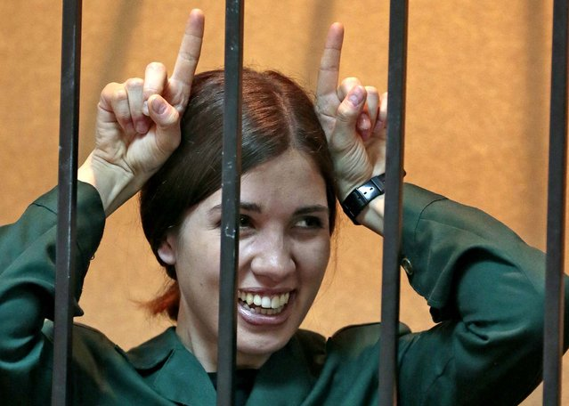 Nadezhda Tolokonnikova, a member of the feminist punk band p*ssy Riot, gestures from behind bars at a district court in Zubova Polyana, on April 26, 2013. Tolokonnikova, in custody since her arrest in March 2012, is serving a two-year sentence for the band's irreverent protest against President Vladimir Putin in Moscow's main cathedral.  A Russian court is to consider whether she is eligible for early release. (Photo by Mikhail Metzel/Associated Press)