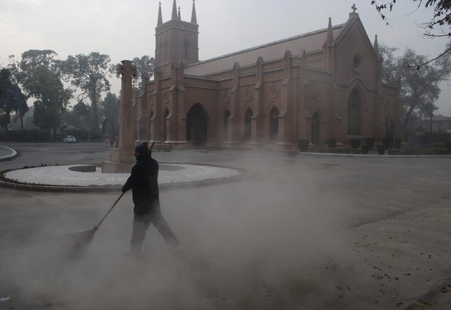 A man cleans the ground outside the St Johns Cathedral Church, on Christmas eve in Peshawar December 24, 2014. (Photo by Khuram Parvez/Reuters)