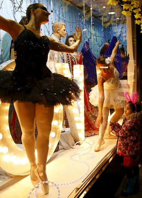A girl watches ballerinas perform in a shop window during Diwali celebrations in Leicester, Britain November 11, 2015. (Photo by Darren Staples/Reuters)