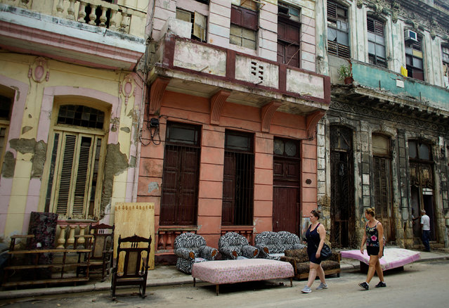 Tourists walk past furniture let to dry on the street after Hurricane Irma caused flooding and a blackout, in Havana, Cuba September 11, 2017. (Photo by Alexandre Meneghini/Reuters)
